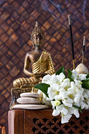 buddha idol with incense sticks stones and orange blossom flowers against bamboo background photo