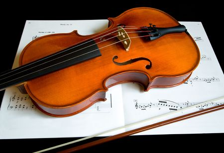 fiddles: Violin and a Bow on a Music Sheet