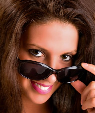 snoop: Smiling Young Brunette Looking over Sunglasses