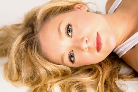 lying on side: Beautiful Blonde Laying on the Floor and Looking at the Camera
