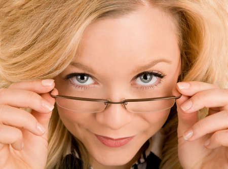 looking over: Beautiful Blonde Looking Over her Glasses Stock Photo
