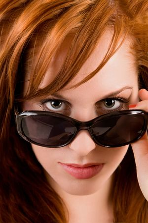 Close-up of a young lady looking over her sunglasses. photo
