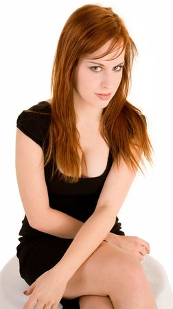 A sexy red hair lady is sitting on a bench looking sideway at the camera. photo