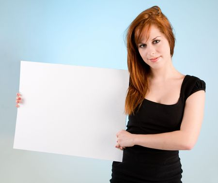 publicize: A beautiful young redhead woman is holding a blank white sign.