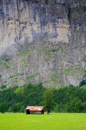 massy: Small Barn close to a Steep Rocky Mountain in Switzerland Stock Photo