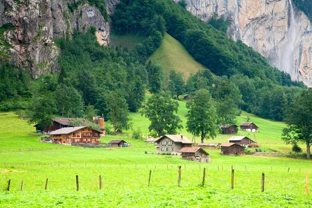 Houses and Barns close to a Steep Rocky Mountain in Switzerland photo