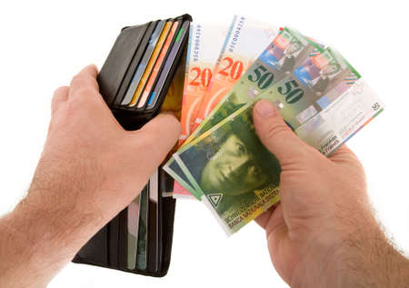 The action of pulling Swiss Francs  out of a wallet isolated on white Stock Photo