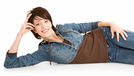 untroubled: A beautiful smiling brunette is lying down and relaxing while looking at the camera.  Stock Photo