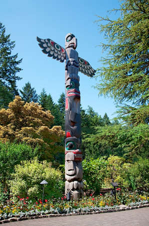 canada aboriginal: Aboriginal Totem Pole stands in the Butchart Gardens, Central Saanich, BC, Canada Stock Photo