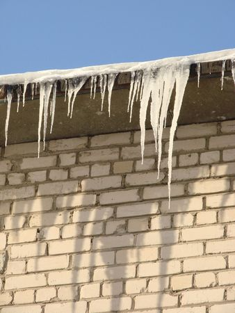dangling: close-up of the icicles dangling from the roof of the house