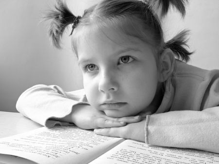 a black and white portrait of the small pretty reading girl photo