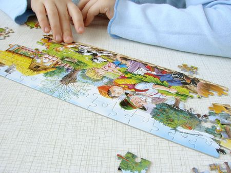 mounting: close-up of the childs hands assembling puzzle