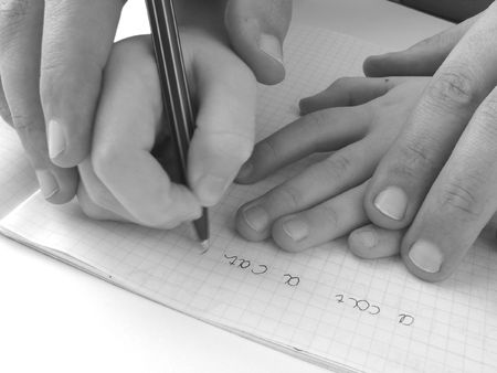 close-up photo of the hands of girl and her father during training to write
