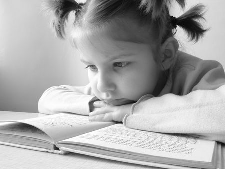 black and white portrait of the small pretty reading girl                                photo
