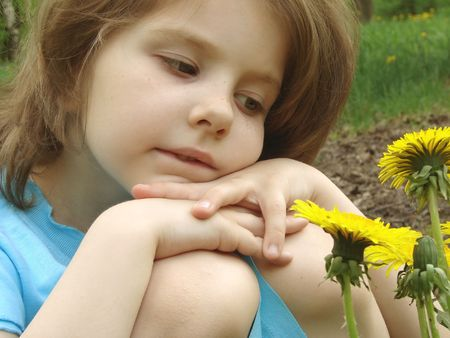 naivete: outdoor portrait of the little pretty girl looking at the flowers