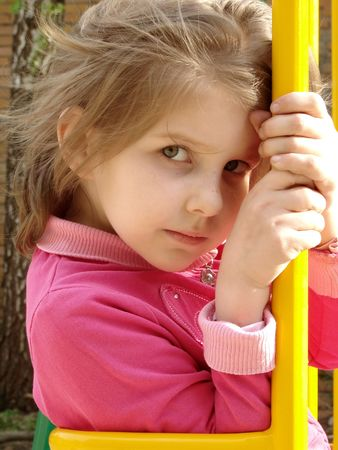 naivete: portrait of the small pretty girl at the playground                                Stock Photo