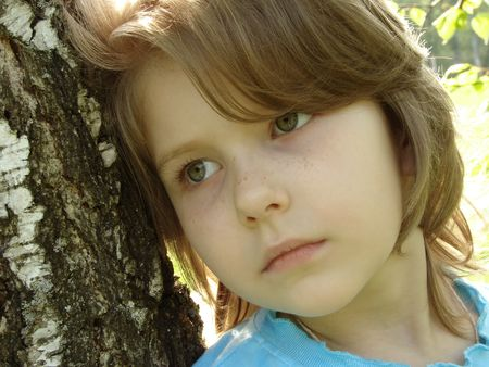 naivete: outdoor portrait of the little pretty girl at the springtime