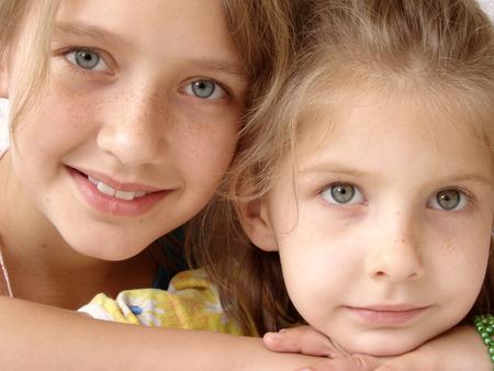 two pretty smiling happy freckly schoolgirls