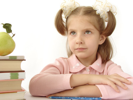 naivete: little pretty thoughtful girl with pile of books