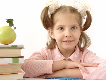 naivete: little pretty smiling girl with pile of books                                Stock Photo
