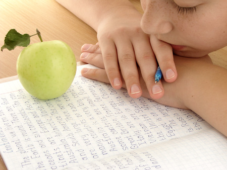 resting schoolgirl with notebook and apple