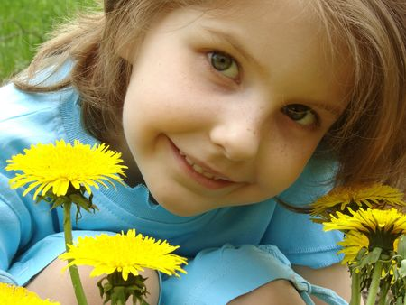 little pretty smiling girl outdoor portrait with dandelions