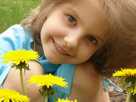 naivete: little pretty smiling girl outdoor portrait with dandelions