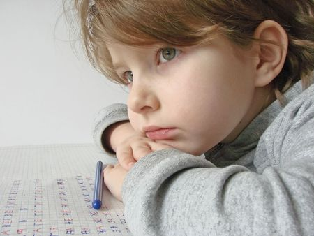 little thoughtful girl with pen and open workbook                                  photo