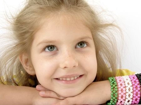 naivete: little pretty smiling girl with colorful bracelet