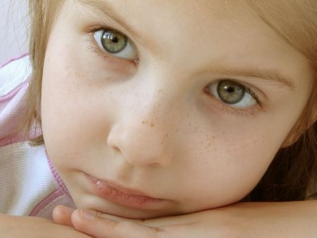 naivete: little pensive girl looking absently                                Stock Photo