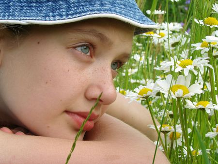 adolescent girl portrait with wild daisies at the summertime meadow                                Stock Photo