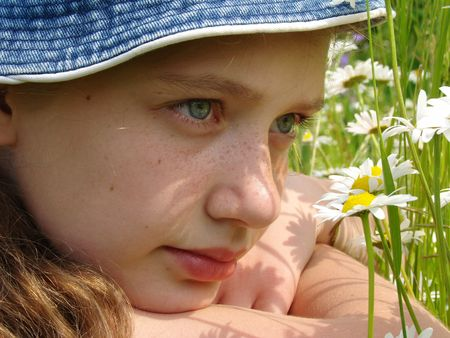 naivete: adolescent girl portrait with wild daisies at the summertime meadow                                Stock Photo