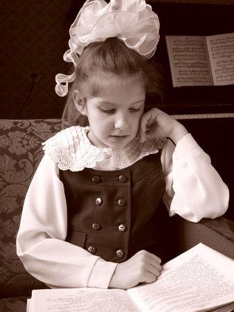 reading schoolgirl with big bow sepia toned portrait