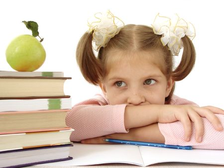 little schoolgirl with pile of books and apple                                Stock Photo