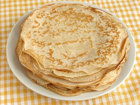 shrove tuesday: pancakes pile on yellow checker tablecloth