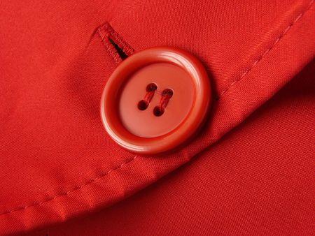 hilo rojo: fragmento de la ropa de color rojo con el bot�n Foto de archivo
