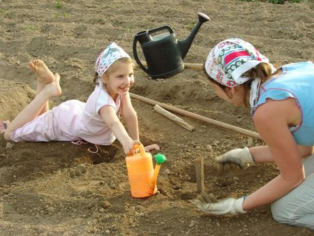 mother and daughter preparing vegetable bed to sowing                                photo