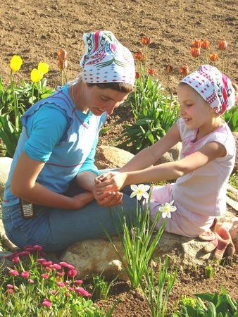 mother and daughter with seeds in hands among the flowers at the rural farm                                photo