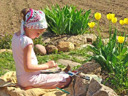 painting nature: young painter paints near yellow tulips