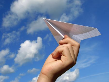 light aircraft: child hand with paper plane against blue sky