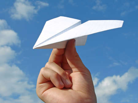 child hand with paper plane against blue sky                                photo