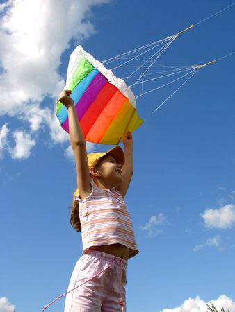 child starts flying kite against blue sky with clouds                                photo