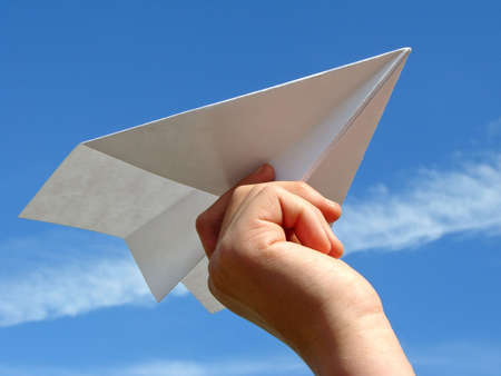 handmade paper: child hand with paper plane against blue sky