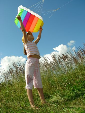 child starts flying kite against blue sky with clouds                                Stock Photo - 5482509