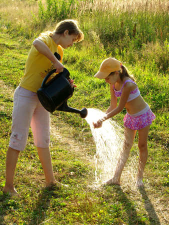 two sisters washing hands and legs from the watering can                                Stock Photo