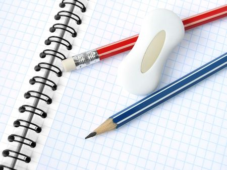 delineate: pencils and eraser on the spiral notepad background
