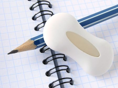 delineate: pencil with eraser on the spiral notepad page