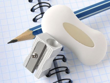 pencil and eraser with sharpener on the spiral notepad page                               photo