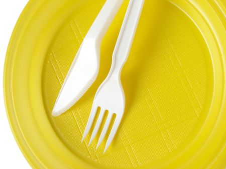 yellow disposable plate with fork and knife                               photo