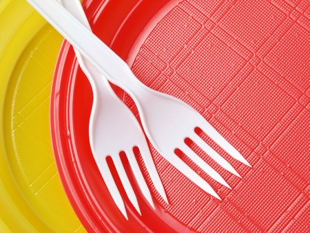 throwaway: red and yellow disposable plates with forks                                Stock Photo